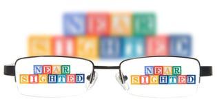 Segni i blocchi con lettere che compitano le miope con un paio dei vetri. Fotografia Stock