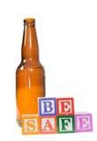 Segni i blocchi con lettere che compitano per essere sicuro con una bottiglia di birra Fotografia Stock