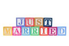 Segni i blocchi con lettere che compitano sposato appena isolato su un fondo bianco Immagine Stock