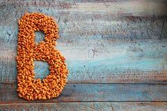 Segni la B con lettere dei fagioli sul bakground della tavola fotografia stock