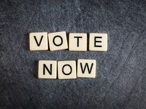 Segni le mattonelle con lettere su ortografia nera del fondo dell'ardesia ora per votare immagine stock