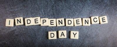 Segni le mattonelle con lettere sulla festa dell'indipendenza nera di ortografia del fondo dell'ardesia immagine stock