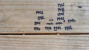 Segni neri del controllo su legno Immagine Stock