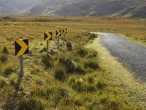 Segni pericolosi della curva stradale Fotografie Stock Libere da Diritti