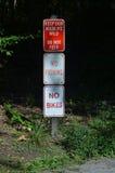 3 segni su un palo: Tenga la nostra fauna selvatica selvaggia nessun'non alimentazione, nessuna pesca, nessun bici Fotografia Stock