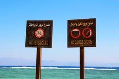 Segni sulla spiaggia nelle lingue inglesi e arabe Fotografie Stock Libere da Diritti