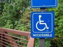 Segno accessibile blu di handicap che appende sulla natura che fa un'escursione percorso fotografia stock