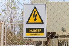 Segno ad alta tensione del pericolo su un recinto Immagini Stock