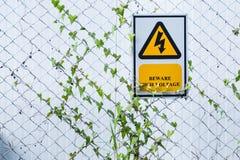 Segno ad alta tensione del pericolo su un recinto thailand Fotografia Stock