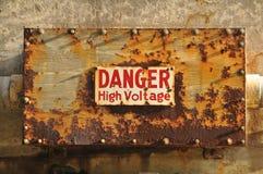Segno ad alta tensione del pericolo su una casella arrugginita Fotografia Stock Libera da Diritti