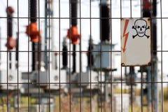 Segno ad alta tensione del pericolo sull'entrata della centrale elettrica Immagini Stock Libere da Diritti