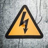Segno ad alta tensione del triangolo sulla parete grigia del metallo Fotografie Stock