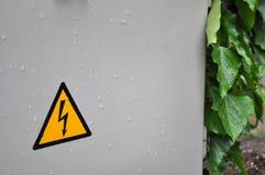 Segno ad alta tensione giallo con la foglia della pioggia Immagini Stock Libere da Diritti