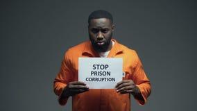 Segno afroamericano di corruzione della prigione di arresto della tenuta del prigioniero, sistema difettoso stock footage