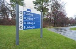 Segno agli edifici per uffici Fotografia Stock