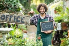 Segno aperto della tenuta maschio del giardiniere dal cartello dell'ufficio Immagini Stock Libere da Diritti