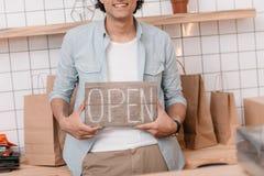 Segno aperto e sorridere della giovane tenuta felice del proprietario di negozio fotografia stock