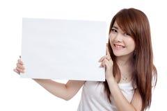 Segno asiatico dello spazio in bianco della tenuta di sorriso della ragazza dal suo lato Immagini Stock Libere da Diritti