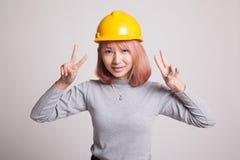 Segno asiatico di vittoria di manifestazione della donna dell'ingegnere con entrambe le mani Fotografie Stock