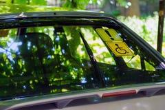 Segno blu del supporto di distintivo L'autoadesivo bianco e blu con un simbolo della sedia a rotelle sopra ha attaccato all'inter fotografia stock libera da diritti