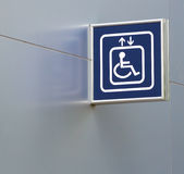 Segno blu dell'elevatore di handicap sulla parete metallica, primo piano Fotografie Stock Libere da Diritti