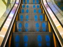 Segno blu di orme sulla scala della scala mobile Fotografia Stock Libera da Diritti