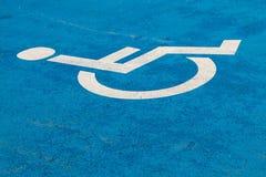 Segno blu di parcheggio di handicap su asfalto per le persone con l'inabilità fotografia stock