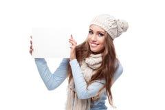 Segno casuale sorridente della holding della ragazza di inverno Immagine Stock