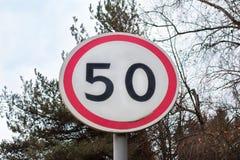 Segno con il limite di velocità sulla strada Immagine Stock