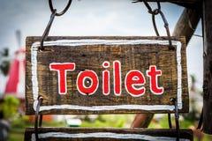 Segno con il testo della toilette sul piatto di legno Fotografia Stock Libera da Diritti