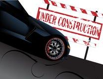 Segno in costruzione con l'automobile del corvette Fotografia Stock