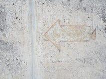 Segno d'annata della freccia sul pavimento del mortaio immagine stock
