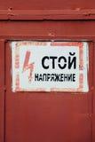 Segno d'annata russo del metallo - fermi, alta tensione del pericolo sul fanno Fotografie Stock