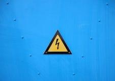 Segno d'avvertimento elettrico giallo del triangolo su fondo blu Fotografia Stock Libera da Diritti