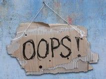 Segno del cartone su un cavo con parole OOPS immagini stock libere da diritti