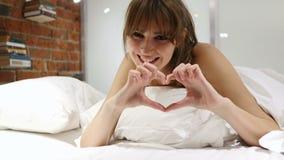Segno del cuore dalla giovane donna che si trova a letto sullo stomaco archivi video