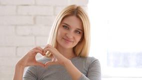 Segno del cuore dalla giovane donna, mani fotografia stock