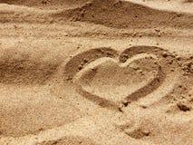 Segno del CUORE fatto con la sabbia su una spiaggia Fotografie Stock Libere da Diritti