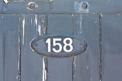 Segno del numero civico 158 sul portone di legno Immagine Stock