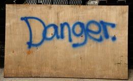 Segno del pericolo dei graffiti dell'inchiostro blu sul bordo di legno Fotografie Stock