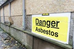 Segno del pericolo dell'amianto a rinnovamento del sito della costruzione di edifici di vecchia costruzione fotografia stock libera da diritti