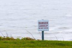 Segno del pericolo per il segno di informazione pubblica accanto alla scogliera del mare Fotografia Stock