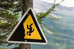 Segno del pericolo su una traccia di montagna nelle alpi Attenzione al precipizio fotografia stock libera da diritti