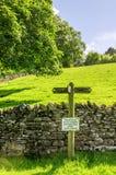 Segno del sentiero per pedoni su un campo verde pendente Immagini Stock