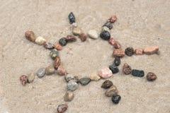 Segno del sole del ciottolo sulla sabbia Immagini Stock Libere da Diritti