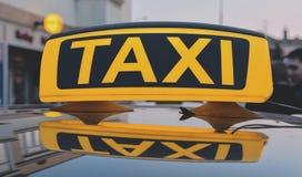 Segno del taxi di Lit sul tetto dell'automobile del taxi nella città Immagine Stock