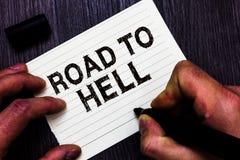 Segno del testo che mostra strada all'inferno Notebo pericoloso rischioso scuro dell'indicatore della tenuta dell'uomo di viaggio immagini stock