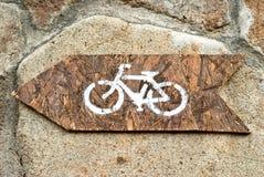 Segno della bicicletta dipinto su una freccia di legno Fotografie Stock Libere da Diritti