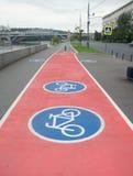 Segno della bicicletta sulla pista ciclabile rossa Fotografia Stock