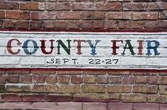 Segno della fiera della contea dipinto sul vecchio muro di mattoni fotografie stock